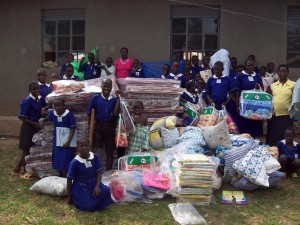 HEADTEACHER AND MATRON PAUSE WITH CHILDREN AFTER RECEIVING THE ITEMS